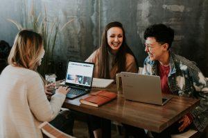 """"""" personnes travaillant ensemble chacune sur un ordinateur portable et riant ensemble"""