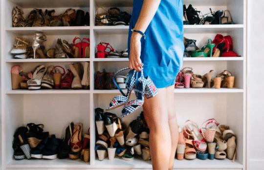 femme portant une robe bleue se tenant devant un placard rempli de chaussures