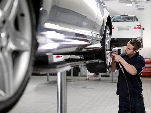Garagiste qui monte des pneus sur une voiture dans un centre de montage