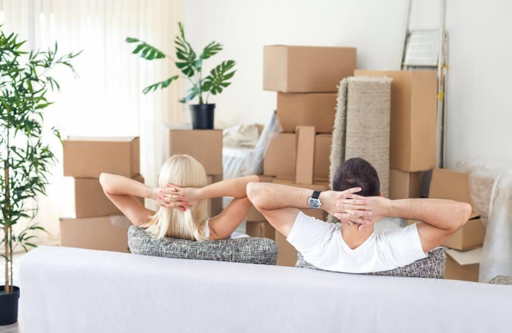 Un homme et une femme vus de dos et assis dans un canapé face à des cartons de déménagement