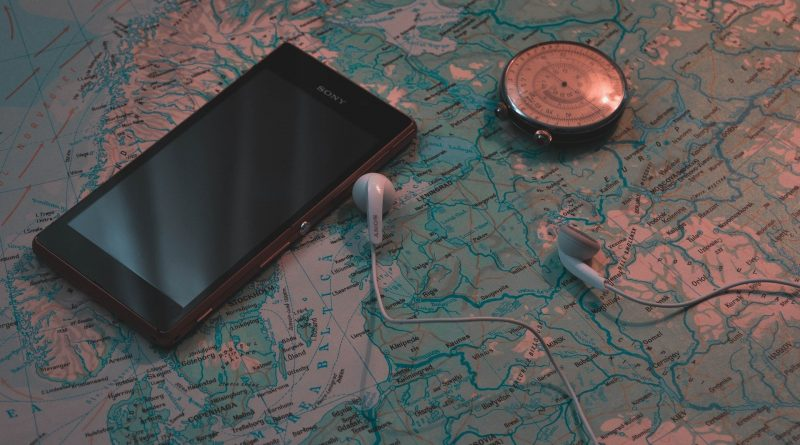 Téléphone posé sur une carte du monde avec des écouteurs et une boussole